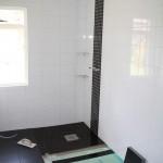 Steg 15: Klinkerläggning Kakel på väggar på plats och golvläggning i full gång. Mosaik bakom blandare.